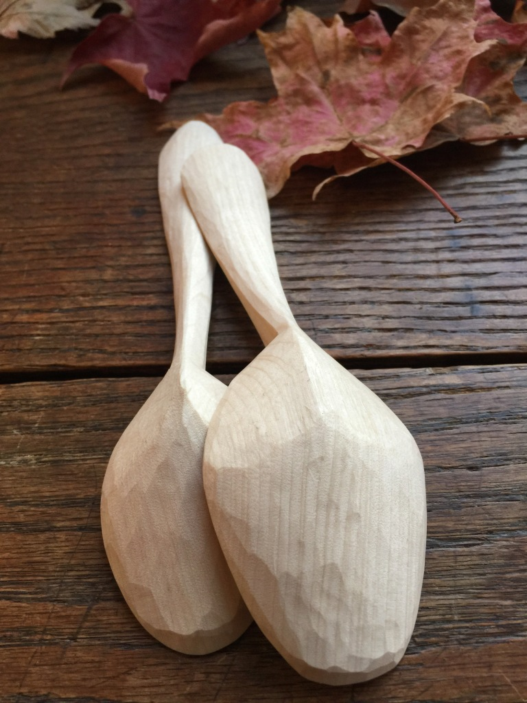 two spoons carved in light-coloured wood