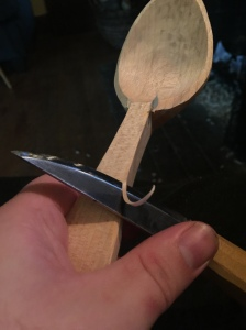 knife slicing the corner off a spoon handle